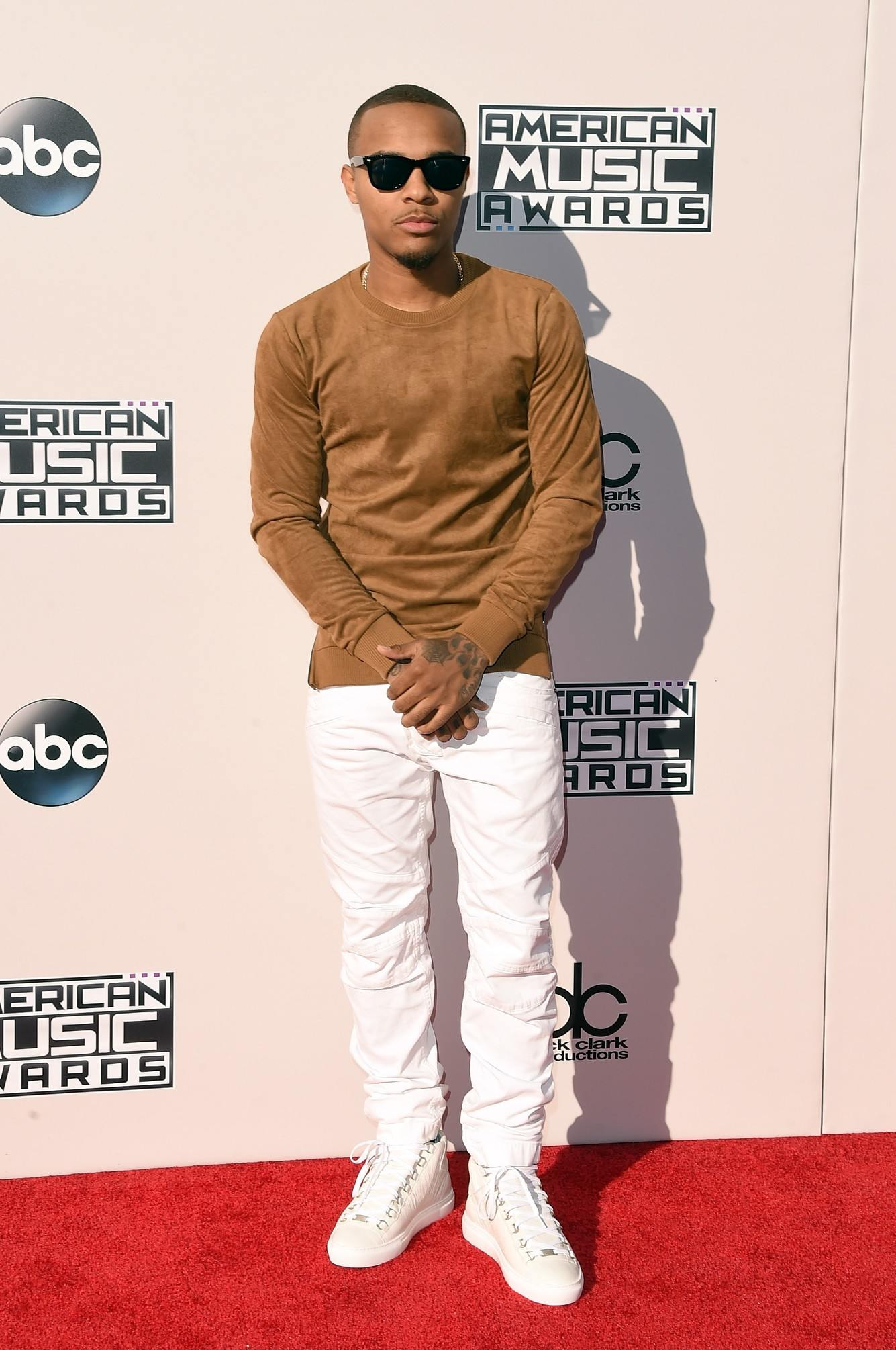 Bow Wow wearing brown top and white pants