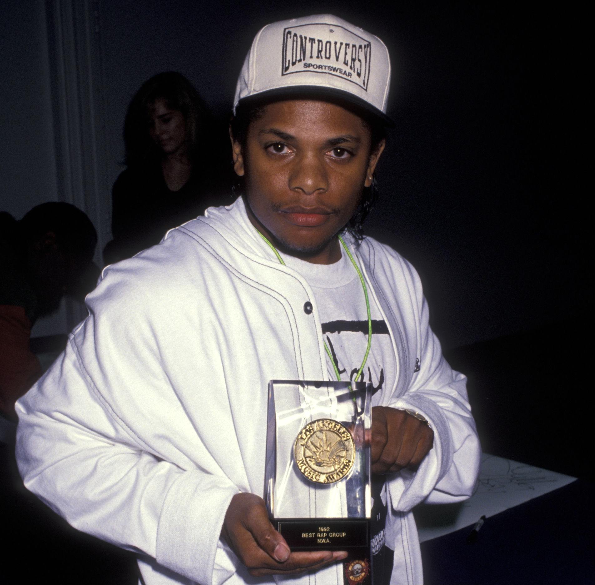 Eazy-E wearing a white jacket holding a plaque