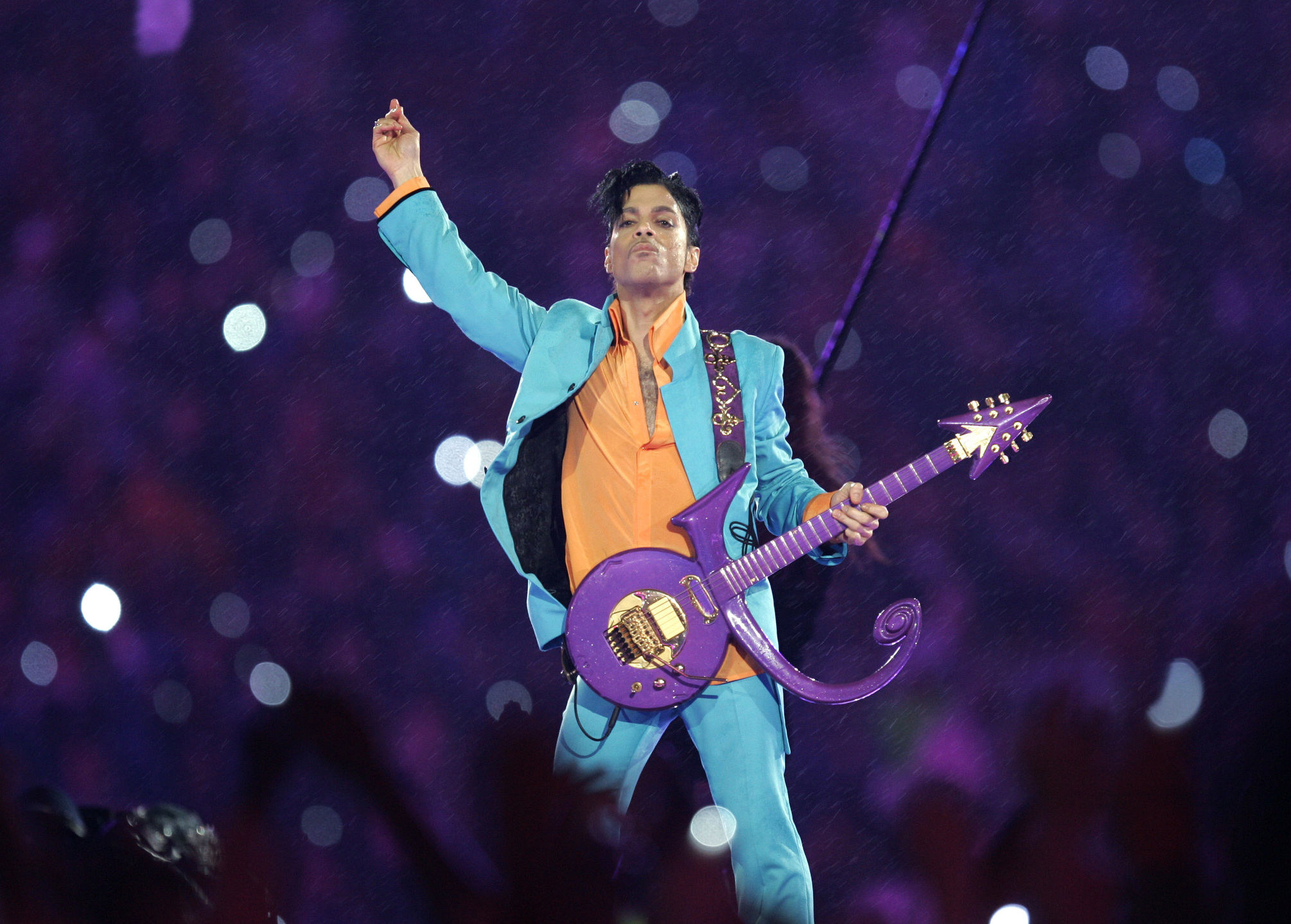 Prince in blue suit and orange shirt
