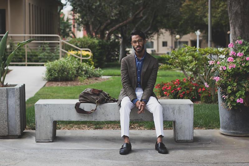 Rajesh wearing blues shirt, brown coat and gray pants