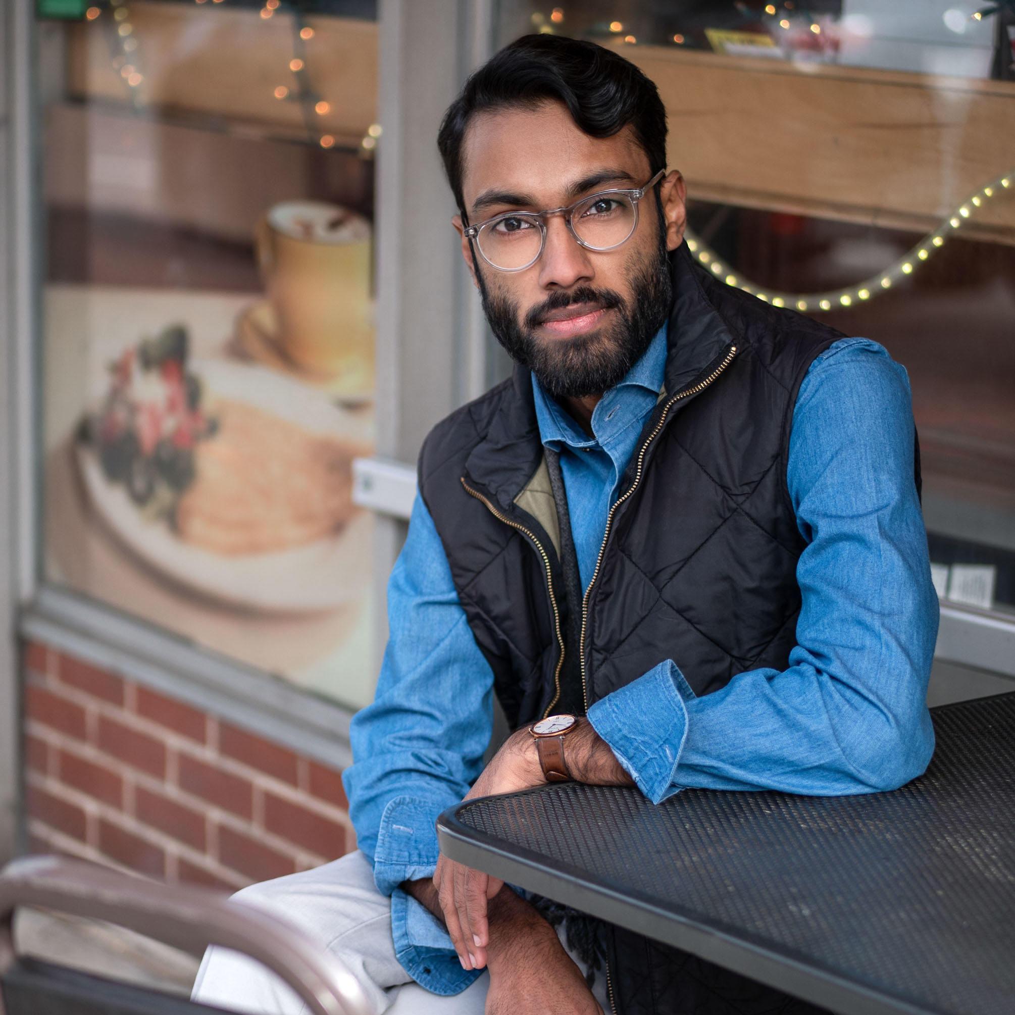 Rajesh wearing blue shirt and black vest