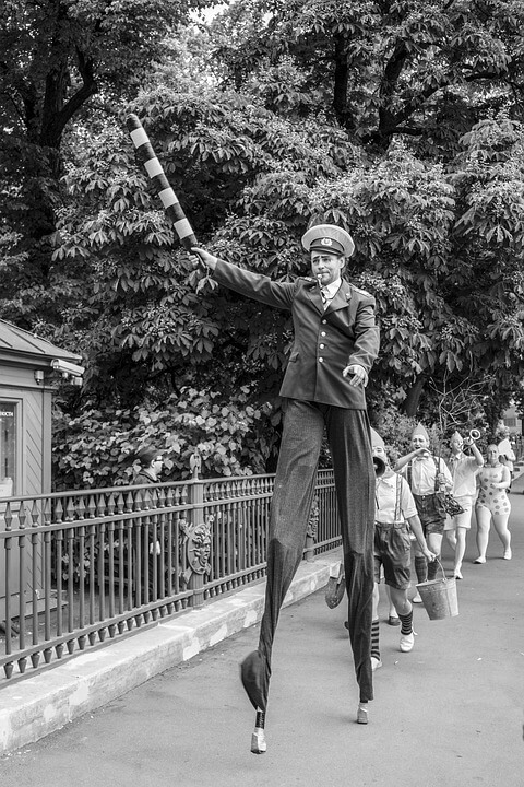 man on stilts leads march