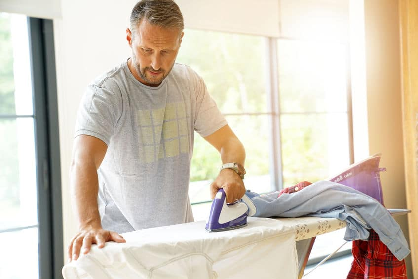 Man at home ironing clothes