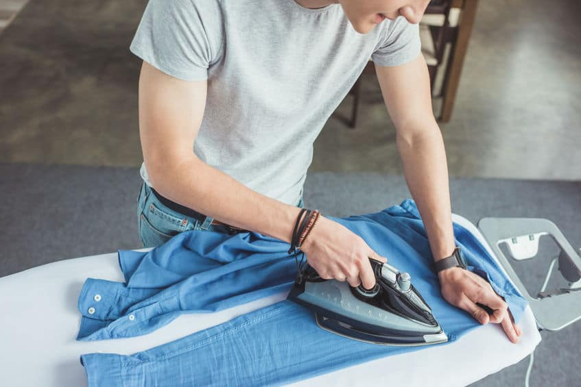 Man ironing blue shirt at home
